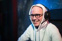 Technologia, hazard, rozrywka, pozwalał ` s sztukę i zaludnia pojęcie - szczęśliwy młody człowiek w eyeglasses z słuchawki bawić  obrazy stock