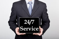 Technologia, internet i networking w biznesowym pojęciu, - biznesmen trzyma pastylka komputer osobistego z 24 7 usługa znakami Obrazy Stock