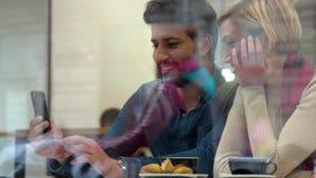 technologia szczęśliwi ludzie z telefonem komórkowym ma zabawę w kawiarni zdjęcie wideo