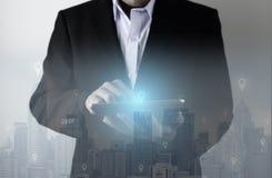 Technologia z biznesowym mężczyzną używa nową pastylkę łączyć z miasta linia horyzontu postu technologią zdjęcie royalty free