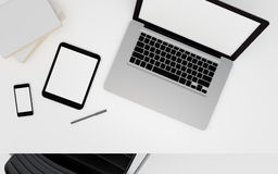 Technologic devices with empty screen on desktop. Laptop, tablet pc and smart phone on office desktop. White empty screen with copy space. 3d rendered Stock Photography
