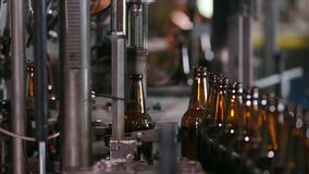 Technological line for bottling of beer in brewery. Electronics checks the quality of bottle on glass factory. Sorting beer bottles. Quality control of glass stock footage