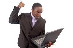 Technological Rage. This is an image of a businessman frustrated at his laptop. This image can be used to represent Slow Laptop Internet fraud etc Royalty Free Stock Photography