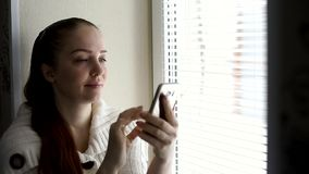 Technologie cyfrowe i komunikacje, w ?rednim wieku kobieta wyszukuje strony internetowe na smartphone ekranie, siedzi obok zdjęcie wideo