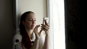 Technologie cyfrowe i komunikacje, w ?rednim wieku kobieta wyszukuje strony internetowe na smartphone ekranie, siedzi obok zbiory wideo