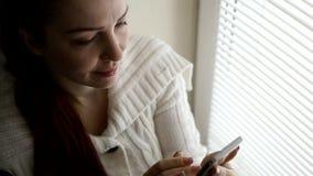 Technologie cyfrowe i komunikacje, w ?rednim wieku kobieta wyszukuje strony internetowe na smartphone ekranie, siedzi obok zbiory