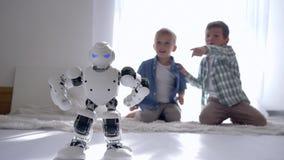 Technologie d'intelligence artificielle, petites danses de robot sur le fond des enfants curieux s'asseyant sur le plancher à la