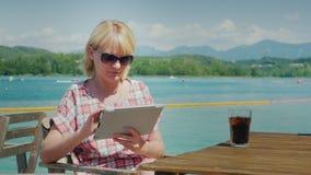 Technologie des vacances Femme avec le comprimé se reposant à une table dans un café sur le fond du lac et des montagnes clips vidéos