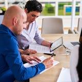 Technologie, die während des Geschäftstreffens von zwei Berufsführungskräften verwendet wird stockfotos