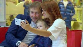 Technologie en mensenconcept - gelukkig jong paar met het winkelen zakken en smartphone die selfie in wandelgalerij nemen Familie stock video