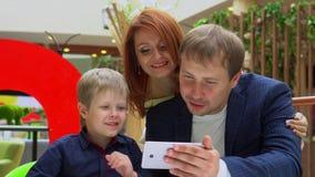 Technologie et concept de personnes - jeune famille heureuse avec les paniers et le smartphone Papa avec le fils dans les achats banque de vidéos