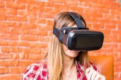 Technologie, gokken, vermaak en mensenconcept - jonge vrouw met virtuele werkelijkheidshoofdtelefoon, controlemechanisme gamepad royalty-vrije stock afbeelding
