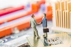 Technologie Informacyjne ochrona lub IT sukces pojęcie Dwa miniaturowego biznesmen IT kierownika trząść ręki podczas gdy stojący  obraz royalty free