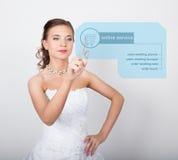 Technologie, Internet en voorzien van een netwerkconcept Mooie bruid met het kapsel van het manierhuwelijk De bruid drukt online Stock Afbeeldingen