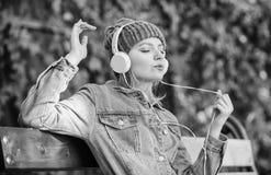 technologie moderne au lieu de la lecture Détendez en parc fille de hippie avec le lecteur mp3 femme de hippie dans le casque Liv photographie stock
