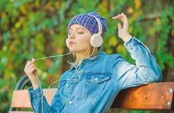 technologie moderne au lieu de la lecture D?tendez en parc fille de hippie avec le lecteur mp3 femme de hippie dans le casque Liv photos libres de droits