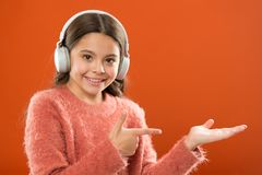 Technologie moderne sans fil d'écouteurs L'enfant de fille écoutent les écouteurs sans fil de musique se dirigeant avec l'index O images stock