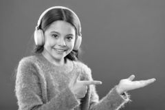 Technologie moderne sans fil d'?couteurs L'enfant de fille ?coutent les ?couteurs sans fil de musique se dirigeant avec l'index O image libre de droits