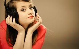 Technologie, musique - jeune fille de sourire dans des écouteurs Photographie stock