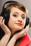 Technologie, musique - jeune fille de sourire dans des écouteurs Photographie stock libre de droits