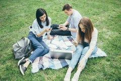 Technologie, onderwijs en Internet-concept - studenten die hun telefoons onderzoeken openlucht stock fotografie