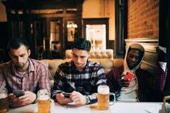 Technologie, online komunikacja i interneta nałóg, Przystojni przyjaciele i ich amerykanina afrykańskiego pochodzenia przyjaciel  obraz royalty free