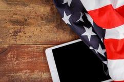 Technologie, Patriotismus, Jahrestag, Nationalfeiertage der Tablette auf amerikanischer Flagge und Unabhängigkeitstag stockfotografie