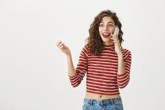 Technologie vereinigt Welt Porträt des begeisterten und aufgeregten kaukasischen Mädchens mit dem gelockten Haar und rotem Lippen lizenzfreies stockbild