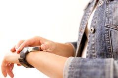 Technologie, Zeit, schnelles Leben Frau in der Denimjacke, die ihre Armbanduhr betrachtet Stockfotografie
