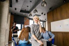 Technologiekonzept blonde Dame sitzt am Ende des Schreibtisches Lizenzfreie Stockfotografie