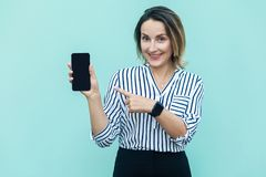 Technologies concept. Cute blonde business woman pointing finger. To new smart phone and looking at camera with toothy smile. Outdoor shot, blue background Stock Photo