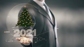 Technologies 2021 disponibles de Holding d'homme d'affaires d'arbre de Noël nouvelles Photographie stock