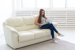 Technologies, freelance and people concept - young woman sitting on the white sofa and chatting in the laptop stock image