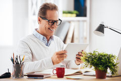 Technologies making life easier. Cheerful mature man holding digital tablet and looking at it with smile while sitting at his working place Stock Photography