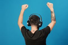 Technologies and music concept. Dj with scorpio tattoo wears headphones. Copy space. Singer listens to music partying. Man holds hands up and dances on blue royalty free stock photography