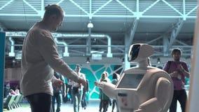 Technologies robotiques modernes Un homme communique avec un robot, presse un bras mécanique en plastique au robot, poignée de ma