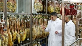 Technologist with butcher checking drying wurst stock video footage