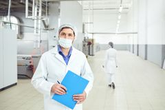 Technologist man at food factory . Technologist men in mask with clipboard in hand at food factory stock photos