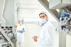 Technologist man at food factory . Technologist men in mask with clipboard in hand at food factory stock image