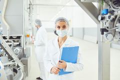 Technologist woman at food factory . Technologist women in mask with clipboard in hand at food factory stock photos