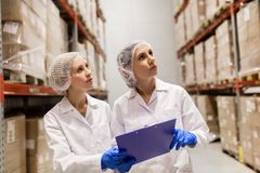 Technologues de femmes à l'entrepôt d'usine de crème glacée  Photos libres de droits