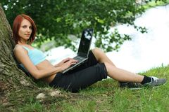 Technology. Cute young girl with laptop outdoors stock image