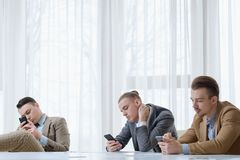Technology addiction business men phone idle. Technology addiction. business men using their phones at office meeting. idle life and work style stock images