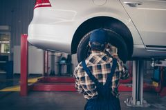 Technology, automotive, safety concept. Rear shot of engineer in. Checkered shirt, hat head wear is torquing lugs nuts of wheel at a garage station, ceiling royalty free stock photo