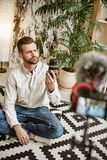 Technology blogger. Vertical portrait of young bearded blogger holding camera lens while recording new episode for his. Vlog. Social Media. Instagram. Youtube stock image