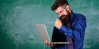 Technology blows his mind. Can not get used to modern technology. Teacher bearded man with modern laptop chalkboard. Background. Hipster teacher aggressive with royalty free stock photo