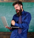 Technology blows his mind. Hipster teacher aggressive with laptop goes mad about modern technology. Can not get used to. Modern technology. Teacher bearded man royalty free stock photography