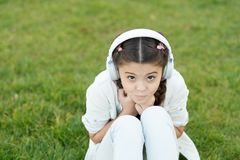Technology can be your best friend. Small child enjoying stereo sound technology on green grass. Little girl listen to. Music playing in earphones on summer stock images
