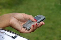 Technology - Cellphone. Girl's hand holding a mobile phone Royalty Free Stock Photography