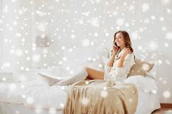 Happy young woman with smartphone in bed at home Royalty Free Stock Images